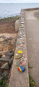 painted stones on wall at Tayport Beach by Caroline Dempster